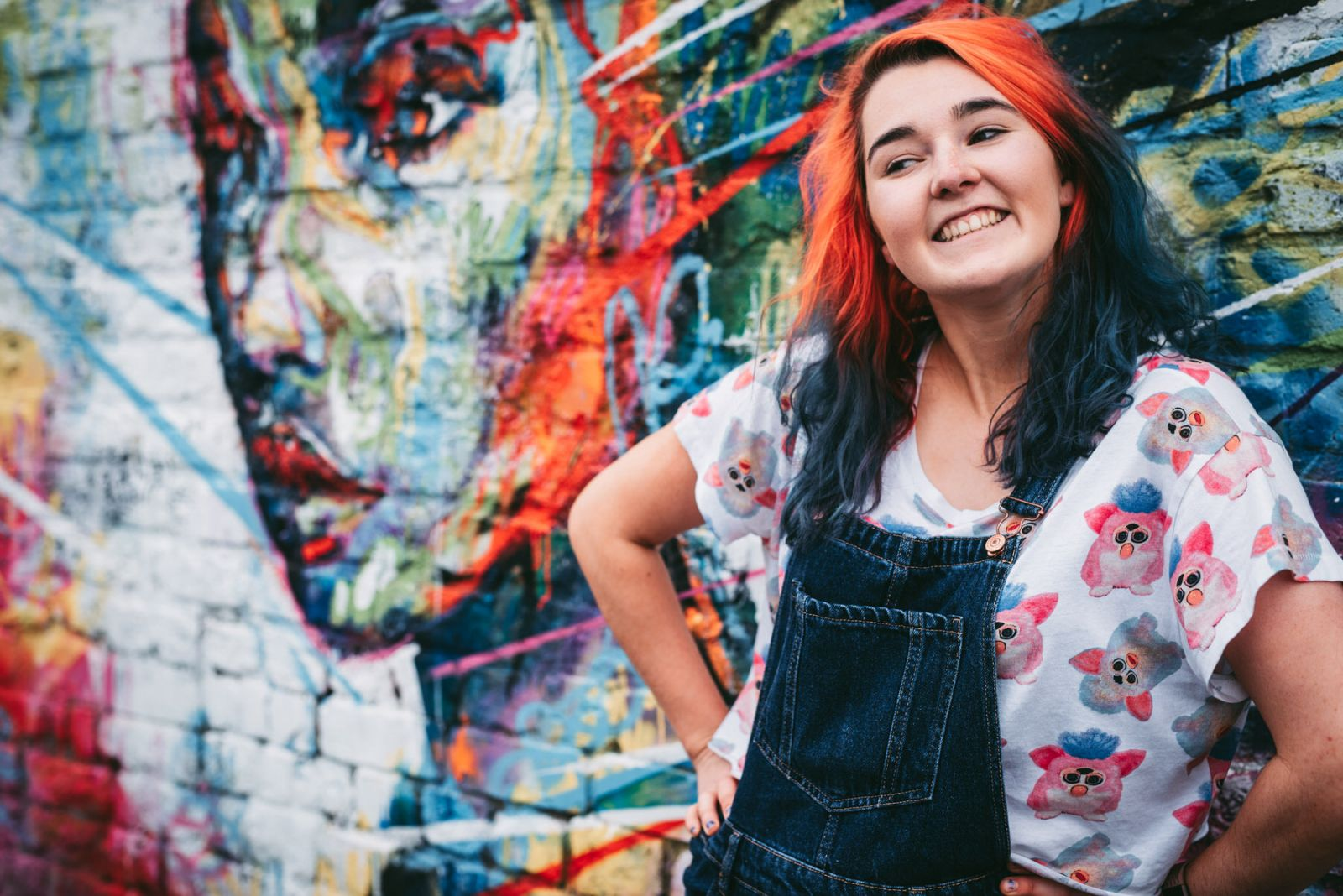 liverpool wedding photographer with red and blue hair smiling for a photo in the baltic triangle area