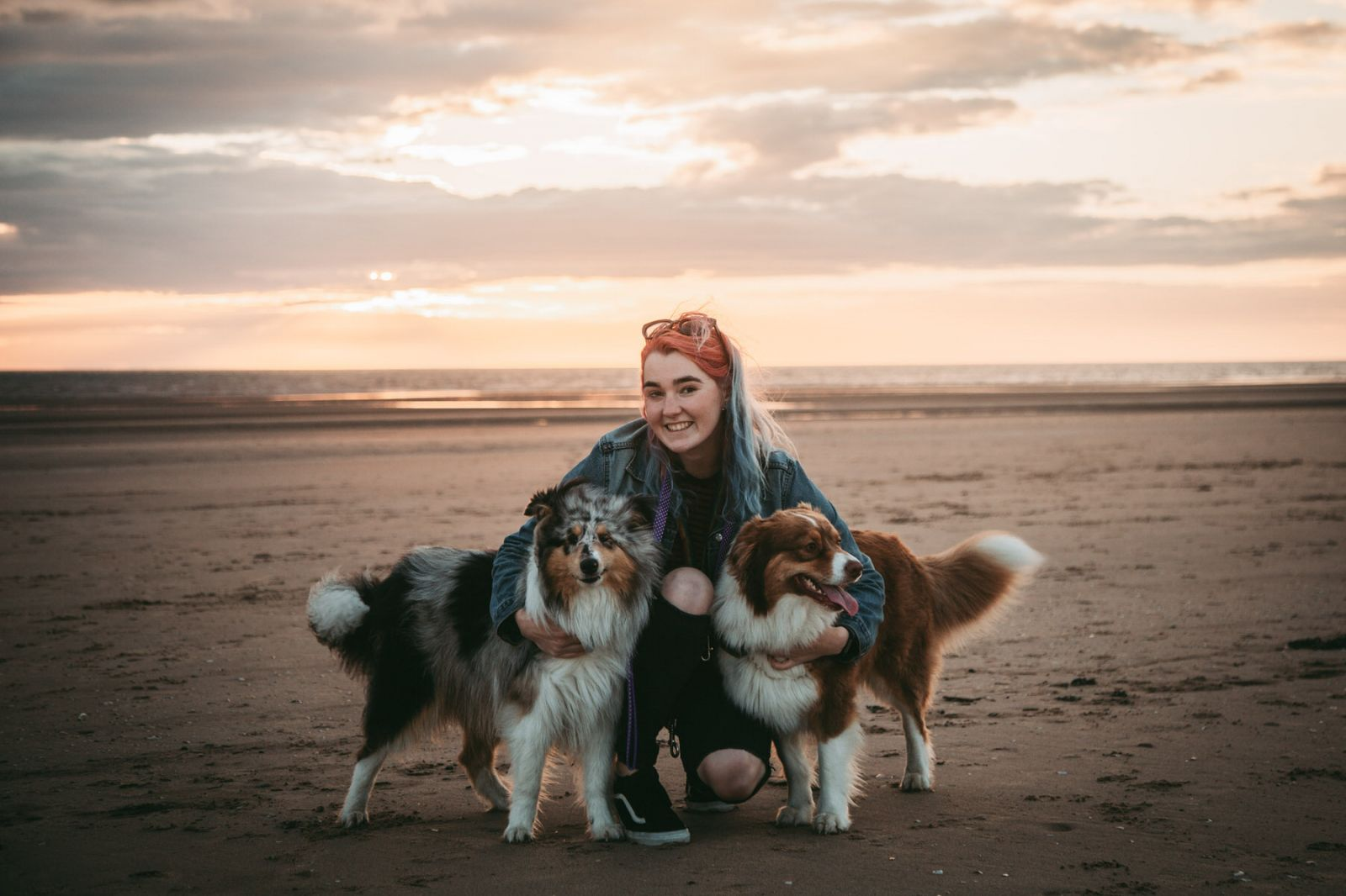 colourful haired liverpool wedding photographer cuddles her dogs at formby beach