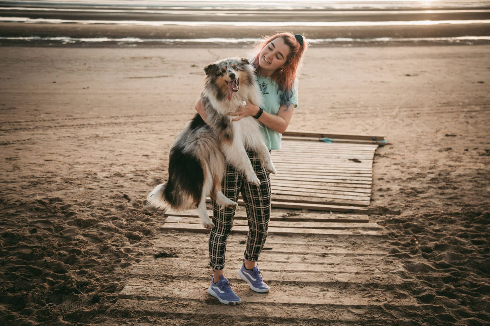 colourful haired liverpool wedding photographer cuddles her dog at formby beach